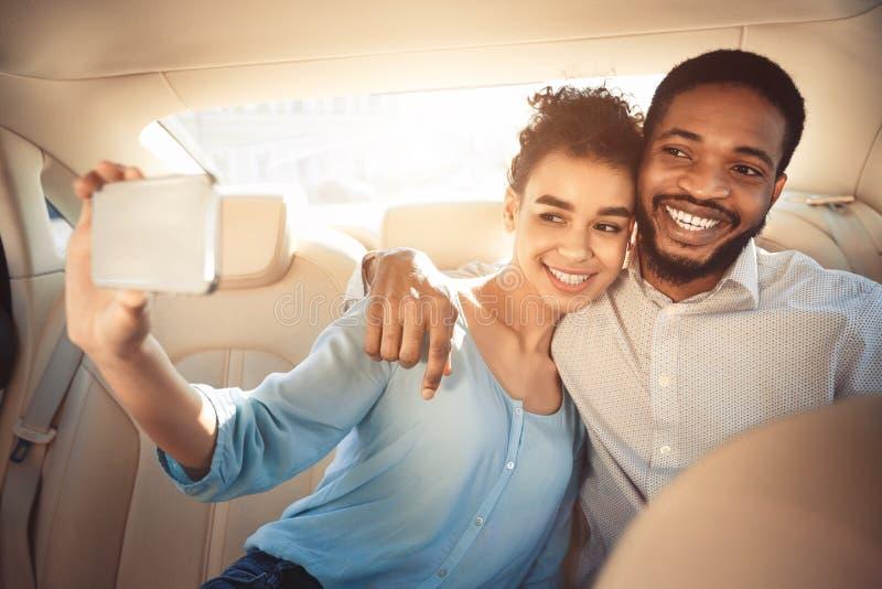 Pares afro-americanos de amor que tomam o selfie, conduzindo no carro imagens de stock
