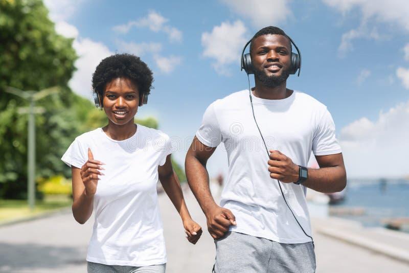 Pares afro-americanos de sorriso que movimentam-se ao longo do banco de rio na manhã fotos de stock royalty free