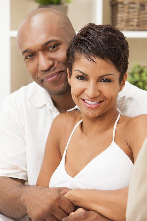 Pares afro-americanos felizes da mulher que sentam-se em casa imagem de stock royalty free