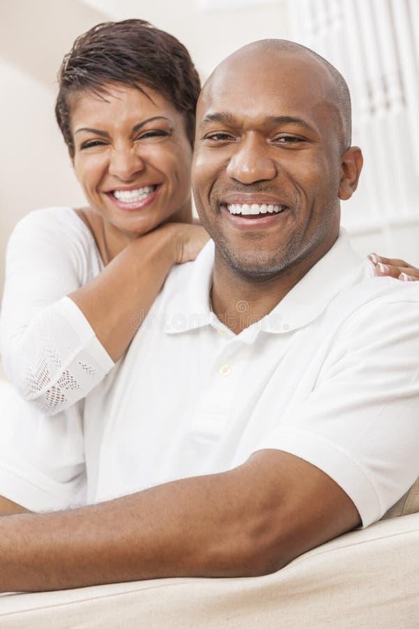 Pares afro-americanos felizes da mulher que sentam-se em casa fotos de stock