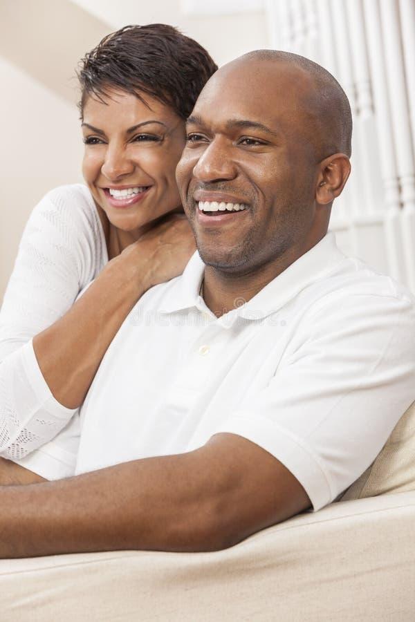 Pares afro-americanos felizes da mulher que sentam-se em casa fotografia de stock