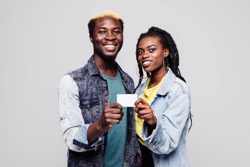 Pares afro-americanos felizes que guardam o cartão vazio pequeno da bandeira ou de crédito que sorri na câmera isolada no fundo b fotografia de stock