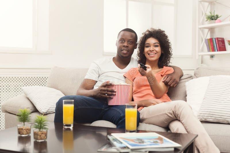 Pares afro-americanos felizes que olham a tevê em casa imagem de stock royalty free