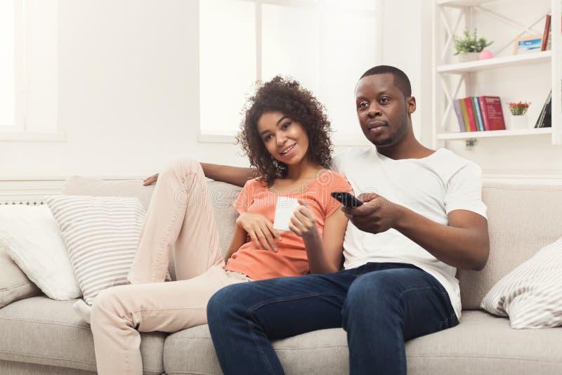 Pares afro-americanos felizes que olham a tevê em casa imagens de stock