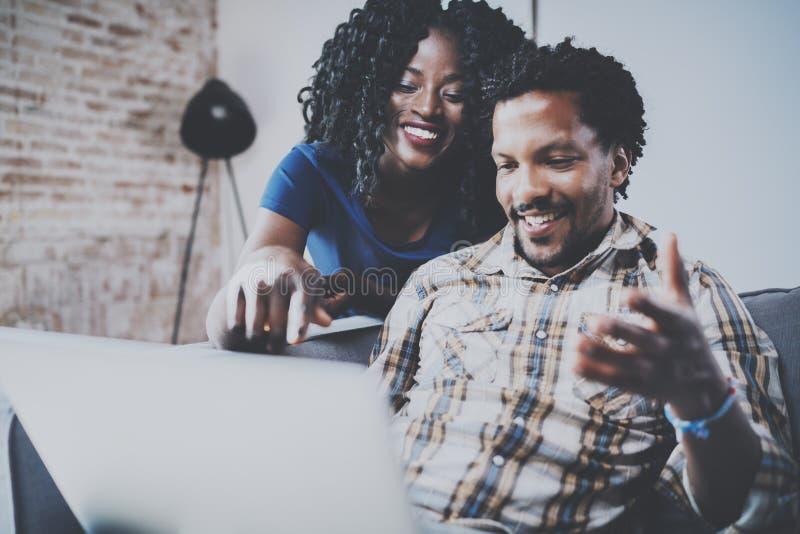 Pares afro-americanos felizes que relaxam junto no sofá Homem negro e menina novos que usa o portátil moderno para o vídeo imagem de stock