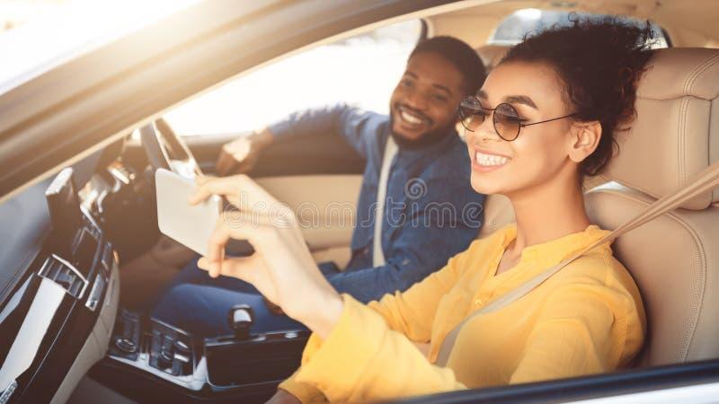 Pares afro-americanos felizes que tomam o selfie no carro imagens de stock