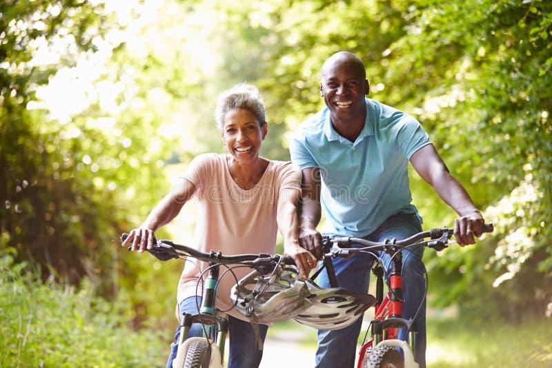 Pares afro-americanos maduros no passeio do ciclo no campo imagem de stock royalty free