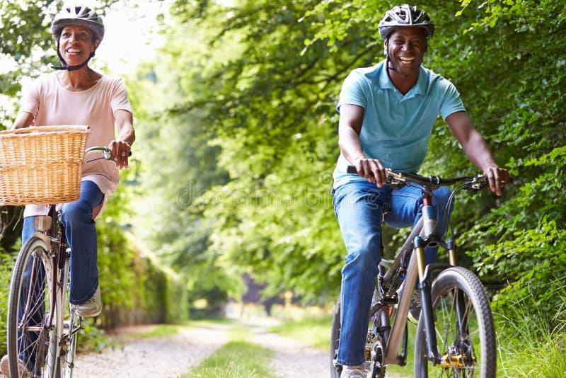 Pares afro-americanos maduros no passeio do ciclo no campo imagens de stock royalty free
