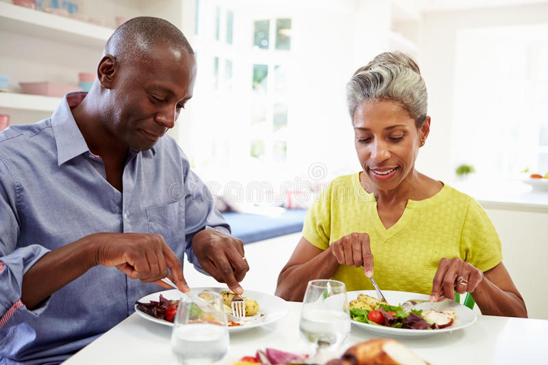 Pares afro-americanos maduros que comem a refeição em casa foto de stock