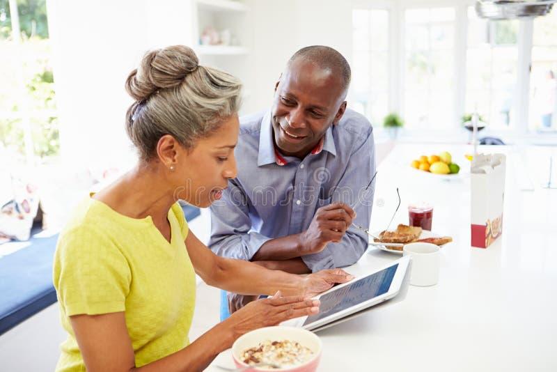 Pares afro-americanos maduros usando a tabuleta de Digitas em casa