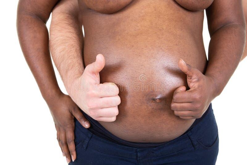 Pares afro-americanos misturados com os polegares acima na barriga africana grávida imagem de stock