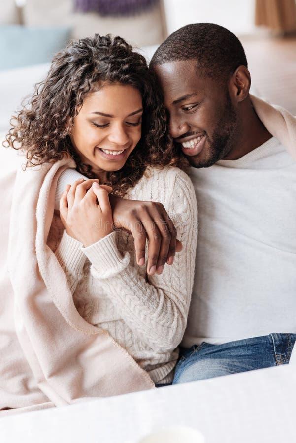 Pares afro-americanos novos bonitos que abraçam no café fotografia de stock royalty free