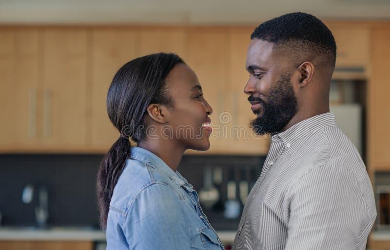 Pares afro-americanos novos de amor que olham nos olhos de cada um fotos de stock