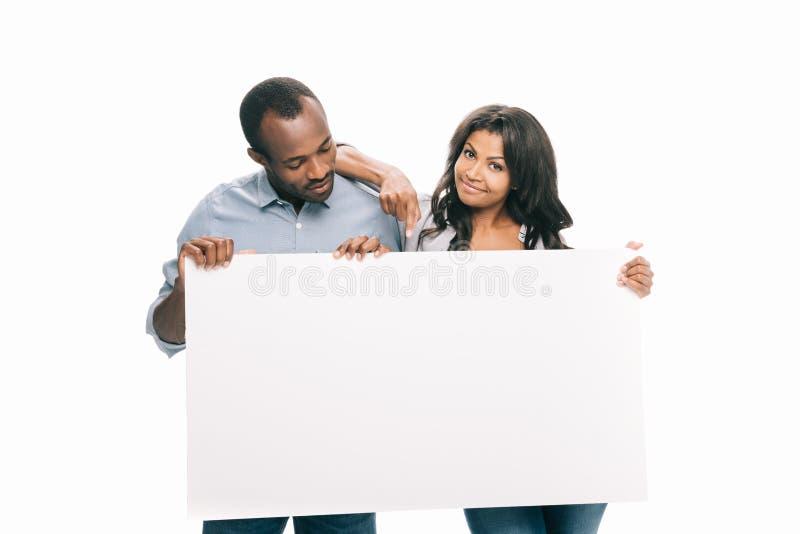 pares afro-americanos novos felizes que guardam a bandeira vazia fotos de stock