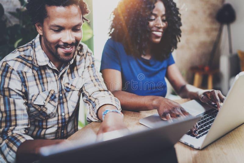 Pares afro-americanos novos felizes usando dispositivos móveis em casa ao sentar-se na tabela de madeira Horizontal, borrado imagem de stock royalty free