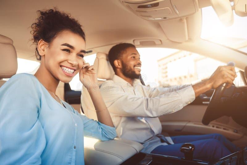 Pares afro-americanos novos que conduzem no carro, viajando junto foto de stock