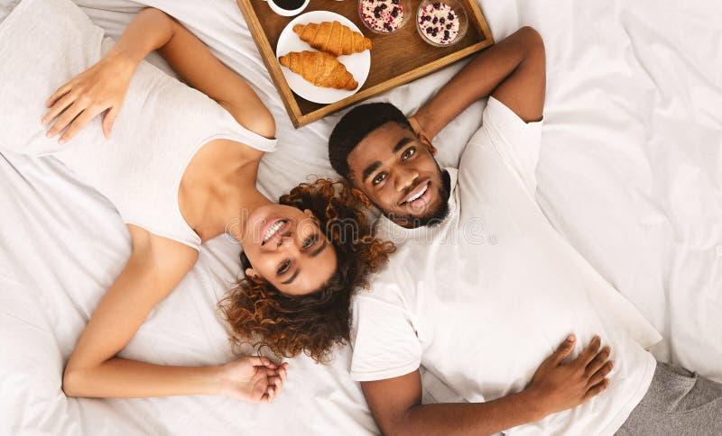 Pares afro-americanos que apreciam o café da manhã saudável na cama imagens de stock