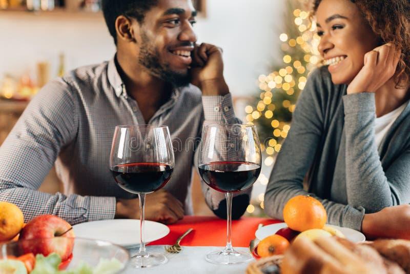 Pares afro-americanos que apreciam o jantar romântico em casa fotos de stock