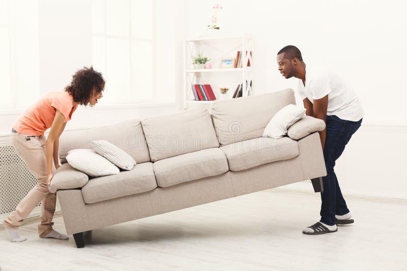 Pares afro-americanos que colocam o sofá na casa nova fotografia de stock royalty free