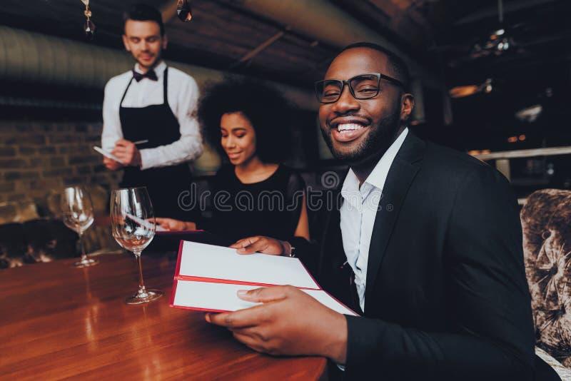 Pares afro-americanos que fazem a ordem no restaurante foto de stock