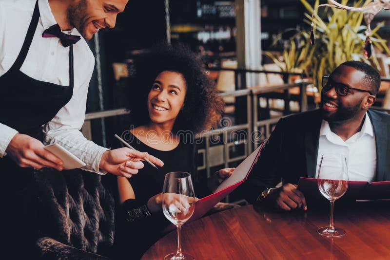 Pares afro-americanos que fazem a ordem no restaurante fotografia de stock