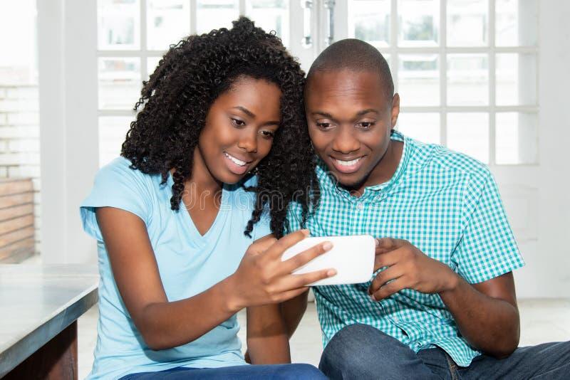 Pares afro-americanos que olham a tevê em linha no telefone imagem de stock