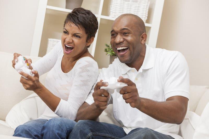 Pares afro-americanos que têm o divertimento que joga o jogo video do console imagens de stock
