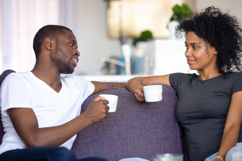 Pares afro-americanos satisfeitos que falam, café bebendo em casa imagem de stock royalty free