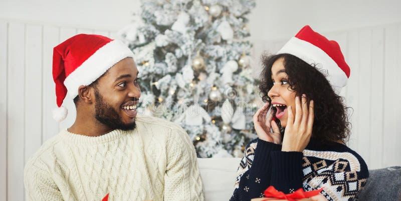 Pares afro-americanos surpreendidos que obtêm presentes de Natal imagem de stock