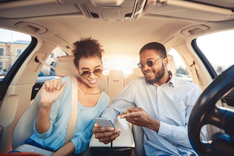 Pares afro-americanos usando o app do navegador no telefone no carro fotografia de stock royalty free