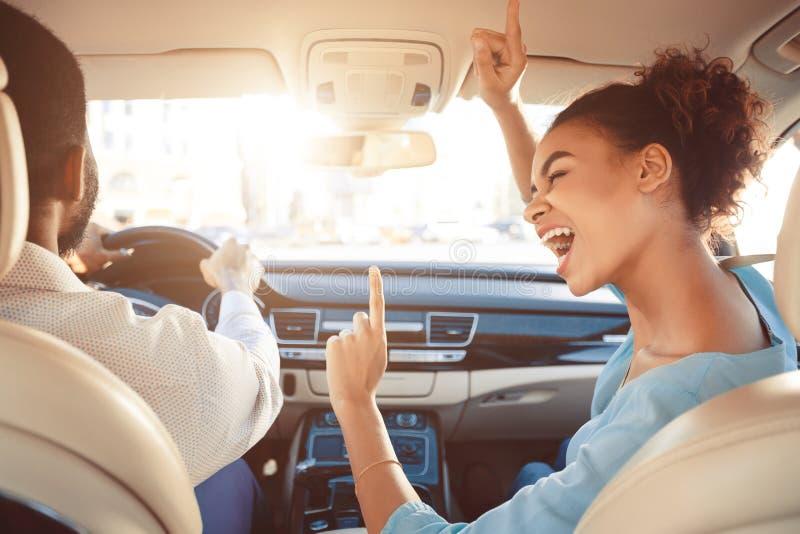 Pares afro felizes que conduzem no carro e na música do canto imagens de stock