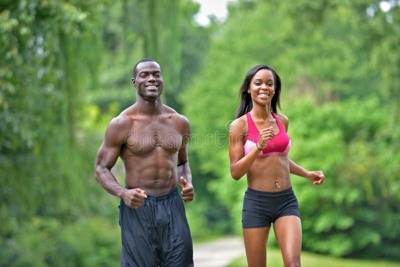 Pares afroamericanos atléticos y aptos - activando en un parque imagen de archivo libre de regalías