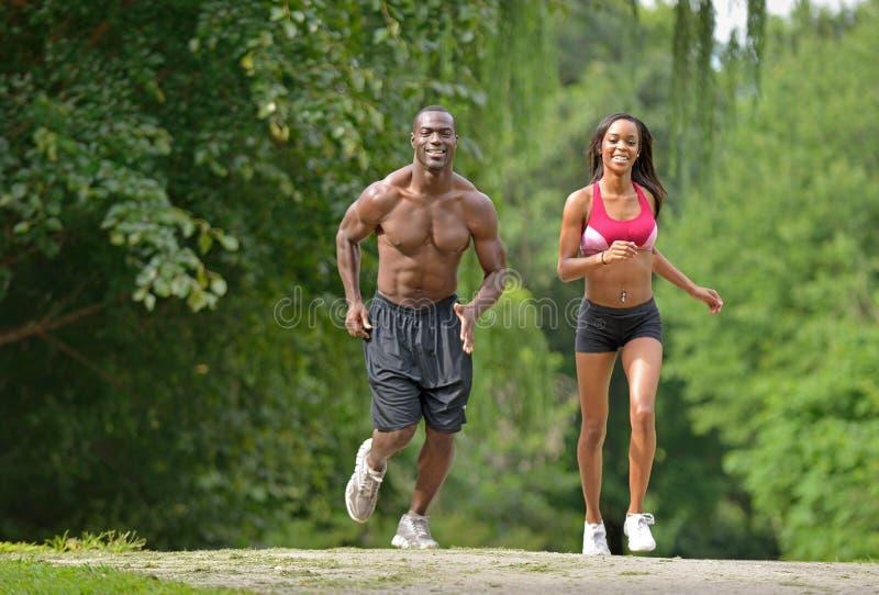 Pares afroamericanos atléticos y aptos - activando en un parque foto de archivo libre de regalías