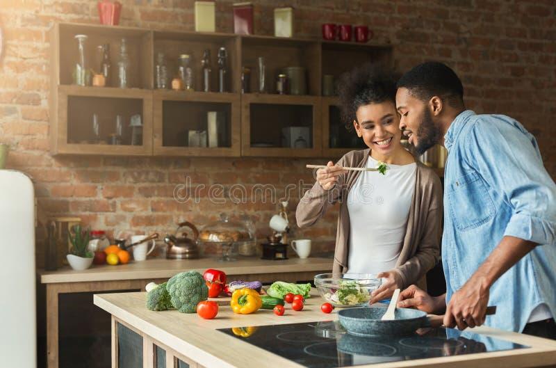 Pares afroamericanos cariñosos que preparan la cena en cocina del desván imagen de archivo