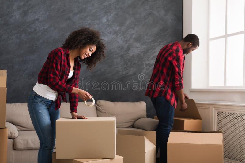 Pares afroamericanos con las cajas del cartón en sitio foto de archivo libre de regalías