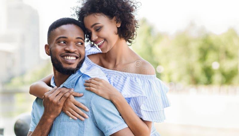 Pares afroamericanos de amor en el amor que abraza en parque imagen de archivo