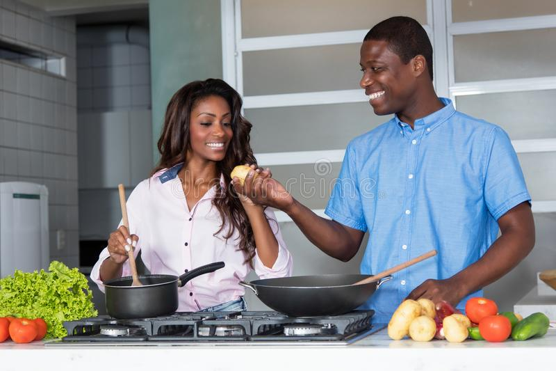 Pares afroamericanos de risa del amor que cocinan en la cocina imágenes de archivo libres de regalías