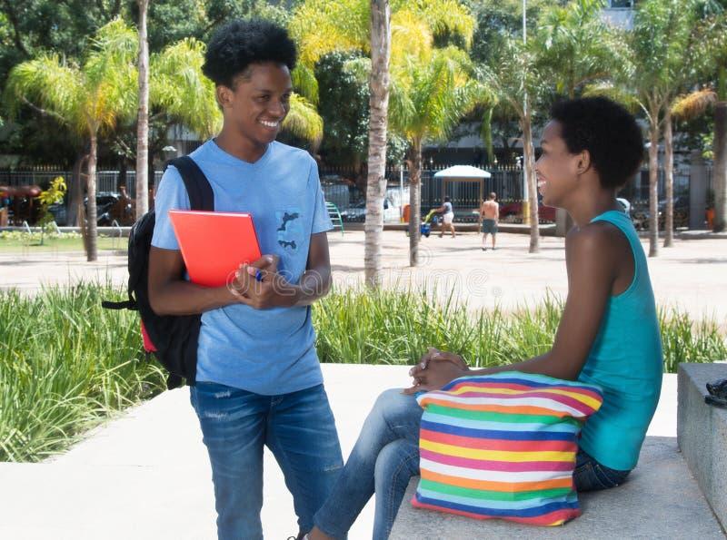 Pares afroamericanos del estudiante que hablan en el campus de la universidad fotografía de archivo