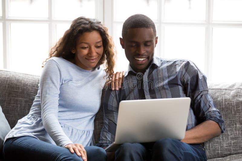 Pares afroamericanos felices en amor usando el ordenador portátil junto fotos de archivo