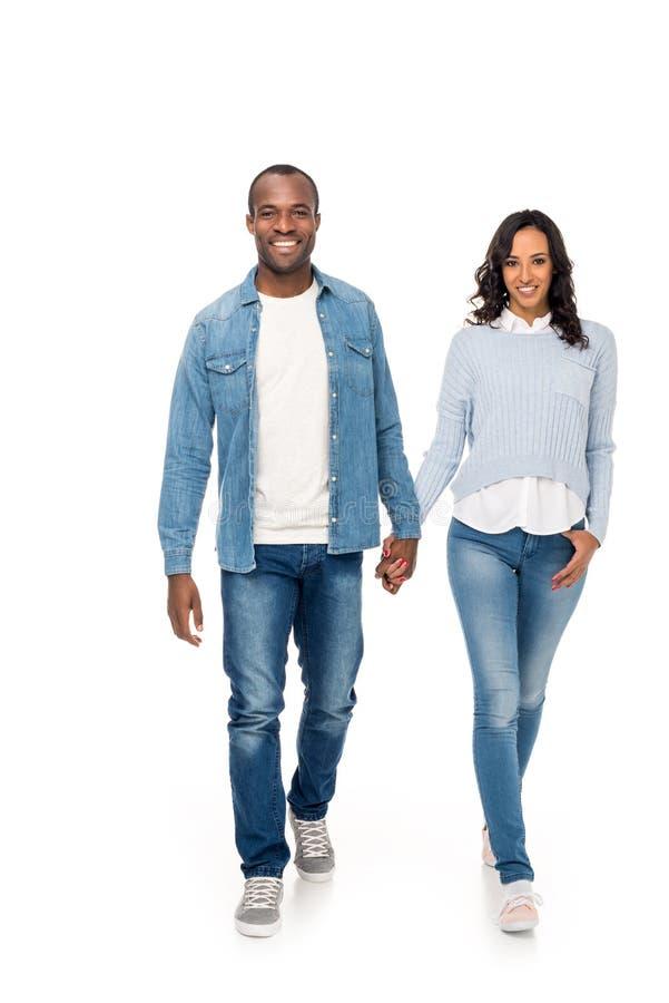 pares afroamericanos felices hermosos que llevan a cabo las manos y que caminan junto foto de archivo