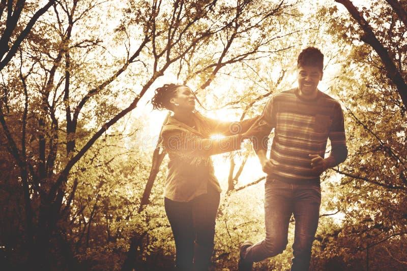 Pares afroamericanos felices que corren y que cogen en el PA foto de archivo libre de regalías