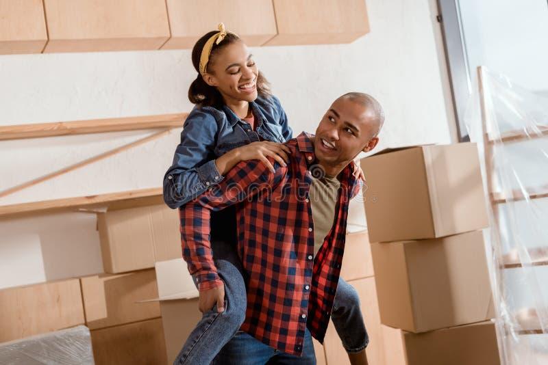 pares afroamericanos felices que llevan a cuestas en el nuevo apartamento imagenes de archivo