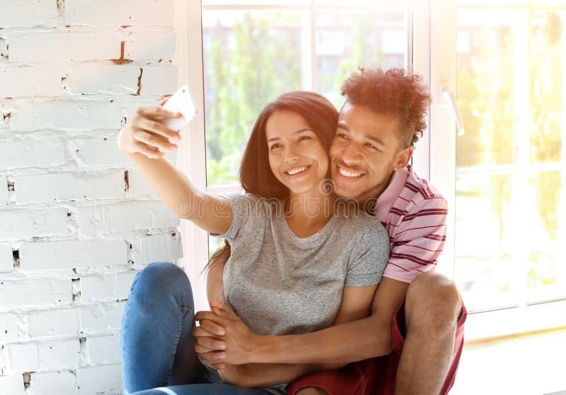 Pares afroamericanos felices que toman el selfie en casa imagen de archivo libre de regalías