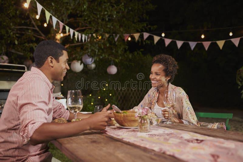 Pares afroamericanos jovenes en una tabla de cena en jardín imagen de archivo