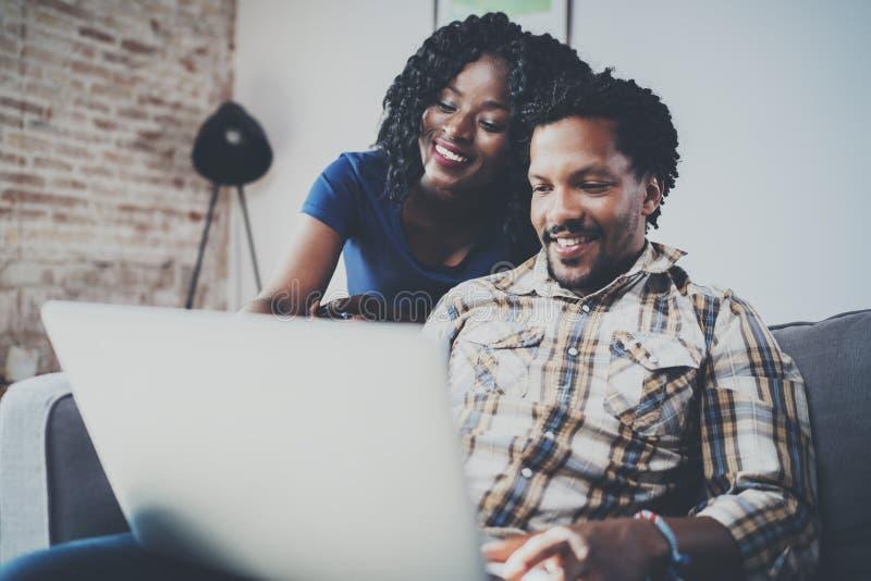 Pares afroamericanos jovenes felices usando el ordenador móvil en casa mientras que se sienta en el sofá Horizontal, empañado fotos de archivo
