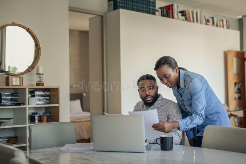 Pares afroamericanos jovenes que hacen sus actividades bancarias en línea en casa imágenes de archivo libres de regalías