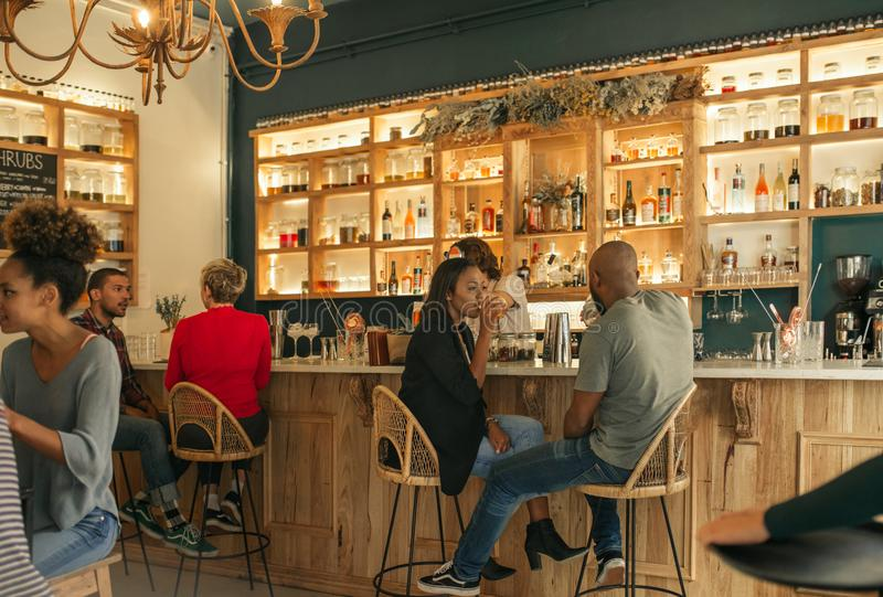 Pares afroamericanos jovenes que tienen bebidas junto en una barra imagen de archivo