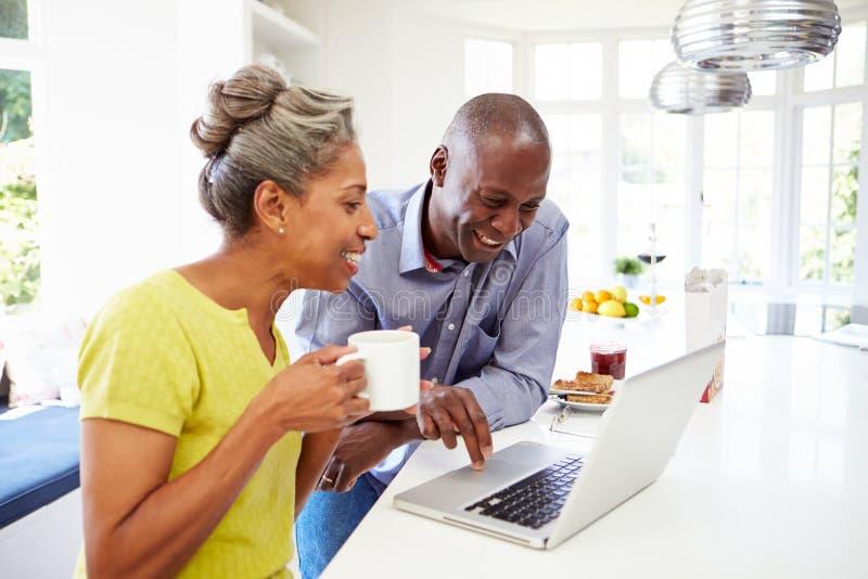 Pares afroamericanos maduros usando el ordenador portátil en Bre imagen de archivo