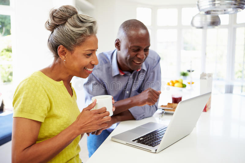 Pares afroamericanos maduros usando el ordenador portátil en Bre