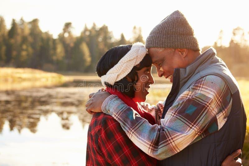 Pares afroamericanos mayores que caminan por el lago imagen de archivo